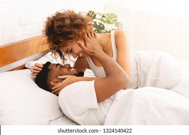 Love and comfort. Happy african-american young couple lying in bed and kissing, free space