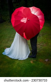 Love concept: Bride and groom kiss behind red heart umbrella, back lit with off camera flash