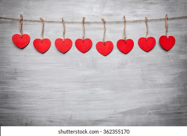 Love concept. Hearts hanging on a string, shot on grey background