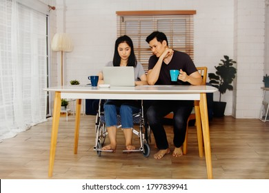 Love concept of a physically disabled couple : Handicapped woman sitting in a wheelchair, working in a living room with her boyfriend, caring, and pampering together willingly.