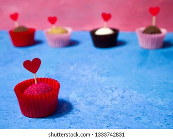 Love concept: truffle chocolates decorated with hearts. Bright romantic dessert. Copy space for your text. In the foreground is a red chocolate truffle garnished with sublimated raspberries.