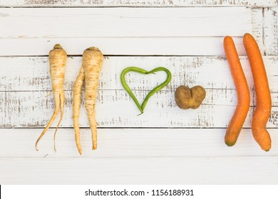 Love concept. Two human shaped parsley roots, carots, spring-bean and potato hearts laying on the old shabby planks painted white. Background. Texture. Vegetables.