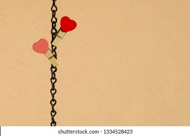 Love concept: Two red and pink clips with heart shape on a steel chain