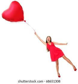 Love concept. Woman flying away with red heart balloon. Funny valentines day image of beautiful cute young woman in red dress. Asian / Caucasian girl isolated on white background in full length.