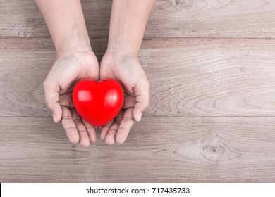 Love Concept : Woman hands holding red heart on brown wooden table background. Free space for text