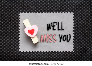"Love conceptual background with wood clips,love shape on grey paper ""We'll miss you"""