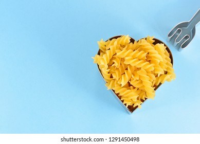 Love cookie cutters with fusilli pasta on blue background. Love and relationship concept with copy space. Homemade Cooking. Food Preparation.Creative Style for designed work. Happiness in the kitchen.