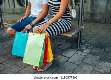 Love couple with bright shopping bags sitting on bench with copy space