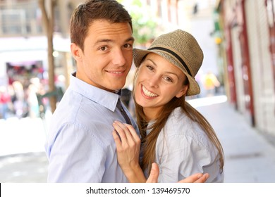 In love couple embracing each other in street