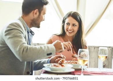Love couple is enjoying pasta in restaurant.