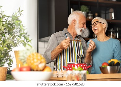 Love couple grandparents cooking together while man feeding his wife at the kitchen. Long lasting relationship concept, Valentine's Day
