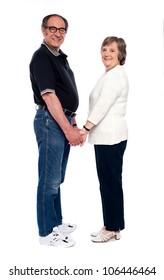 Love couple holding hands. Full length shot isolated over white