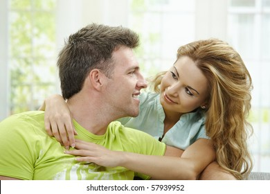 Love couple at home. Man sitting on sofa, his girlfriend embracing him from behind.