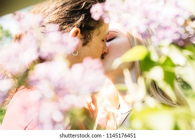 Love couple kissing among blooming lilac