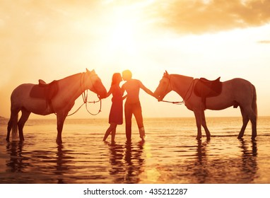 In love couple kissing on the beach. Two horses at sunset, summer scene. sunset in the sea