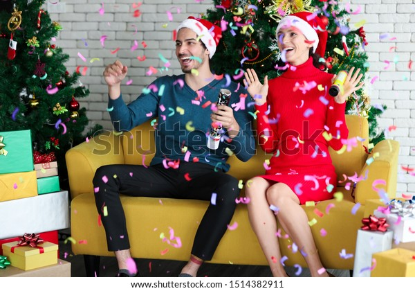 Love couple is launching the colorful confetti into the air during the celebration their christmas in the living room where decorated for Christmas holiday. They have fun and they are so happy.