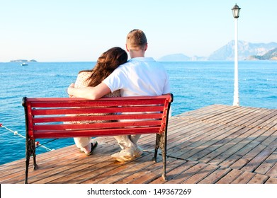 love couple sitting on a bench by the sea embracing