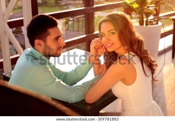 夏のテラスに座って互いに手を取り合い、夕日を眺めながら話し合うレストランに座っている恋人