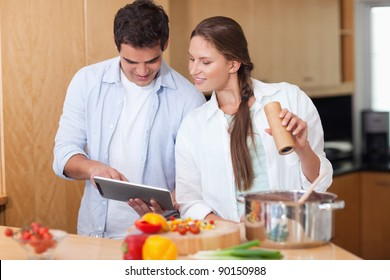 In love couple using a tablet computer to cook in their kitchen