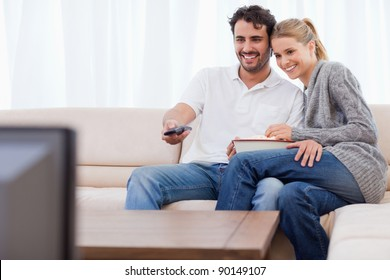In love couple watching TV while eating popcorn in their living room