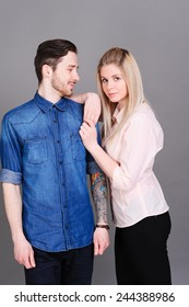 Love couple wearing stylish clothes over gray. Romance.
