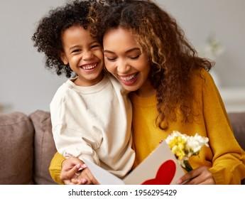 Mit Liebe. Cute aufgeregter kleiner Sohn, der seiner Mutter eine handgemachte Postkarte mit rotem Herzen, glückliche Mutter, die mit dem Kind umarmt, während sie auf dem Sofa zu Hause sitzt. Festtagskonzept für Mütter