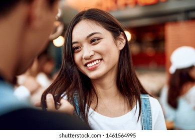 Love and date concept. Young pretty smiling asian woman looking to her beloved man while he holding her hair lock in hand