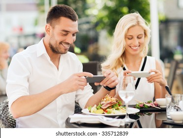 love, date, technology, people and relations concept - happy couple with smatphone taking picture of food at restaurant