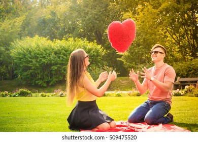 Love and dating. Young fashionable couple lovers having fun with big red heart in park. Picnic concept.
