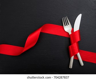 Love dinner silver cutlery. Fork and knife tied with red ribbon on black background, top view.