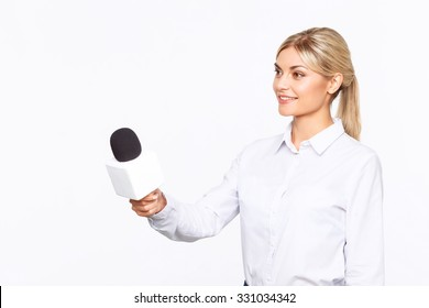 Love doing it. Cheerful content professional Tv announcer holding microphone and interviewing while being busy at work