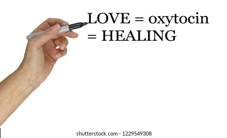 Love equals oxytocin equals healing concept - hand holding marker pen pointing to the words LOVE = oxytocin = HEALING creating awareness about the effects love has on our physical body