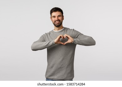 Love, family and care concept. Charming bearded boyfriend express affection and tender feelings, make heart sign over chest and smiling, cherish relationship, adore partner, white background