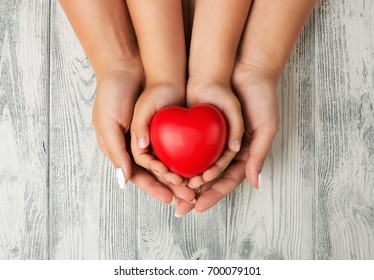 Love, family concept. Close up of mother and children hands holding red rubber heart together