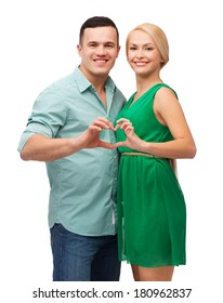 love and family concept - smiling couple showing heart with hands