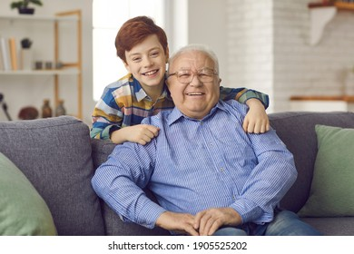 Love and family connection. Family portrait of happy grandfather and little grandson at home in living room. Boy standing behind his grandfather, who is sitting on the couch, hugs his shoulders.