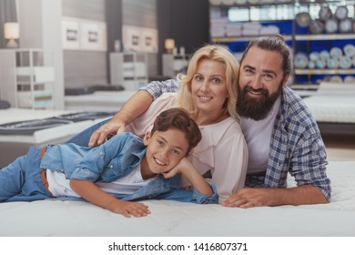Love, family, real estate concept. Happy family smiling to the camera, lying on a new bed at furniture store. Handsome mature man with his wife and son shopping for orthopedic mattress together