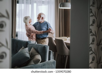 Love feelings in any age. Waist up side on portrait of happy elder husband and wife enjoying time together while dancing in living room at home