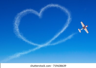 Love figurative heart from a white smoke trail airplane