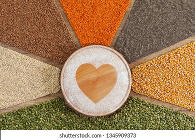 Love food concept - plant based food with diverse grains and seeds surrounding heart shape drawn in flour on round cutting board