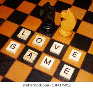 Love Game. Black and white chess knight on an old chessboard