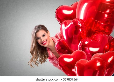 Love girl peeking behind a red balloons, funny Valentine's Day