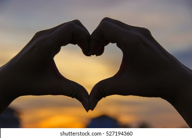 Love. Hand gesture in the form of heart on the background of sunset (Soft focus)