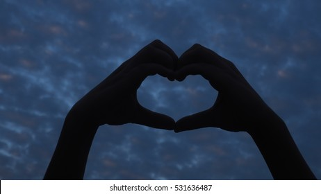 Love. Hand gesture in the form of heart on the background of clouds abstract background
