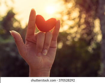 Love hand sign with red heart up to the sunset light and flare