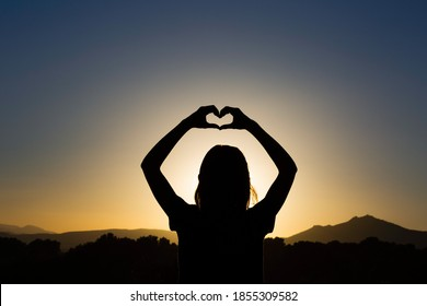 Love with hands. Funny girl silhouette at the sunset doing an heart with her hands. Concept about lifestyle, people, love and nature.  - Shutterstock ID 1855309582