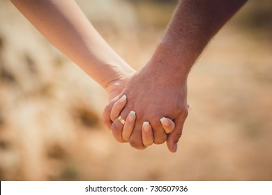 Love hands holding each other in lock of future family close focus picture of man and woman romantic tender touch scene in family stronghold values.