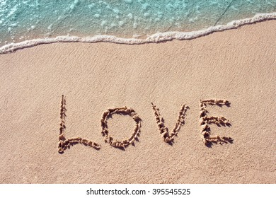 love handwritten on a sandy beach with blue wave on background