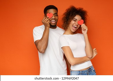 Love and happiness concept. Cheerful enjoyable young couple with little small hearts covering one eye, orange background