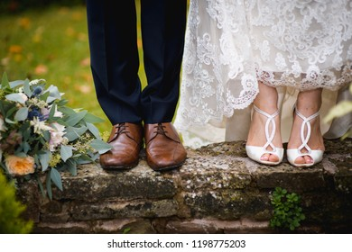 Love and happiness on wedding day. Closeup of bride's and groom's feet and shoes